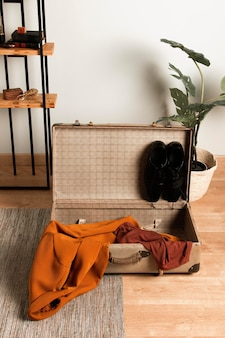 Vintage suitcase with casual clothes on the floor