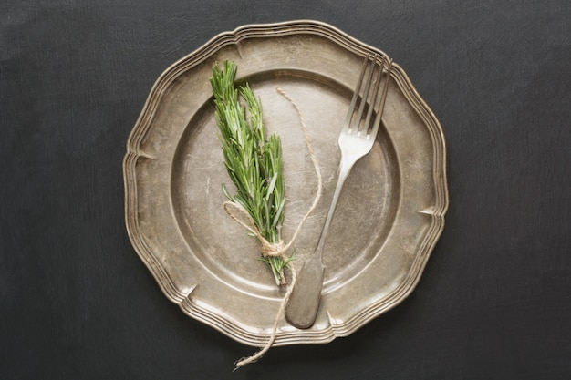 Vintage table place setting with rosemary on black.