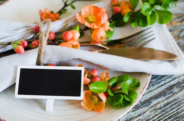 Винтажная сервировка с нежными цветами и тег на деревенском потертый стол.