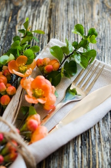 Vintage table setting with delicate flowers on rustic shabby table.