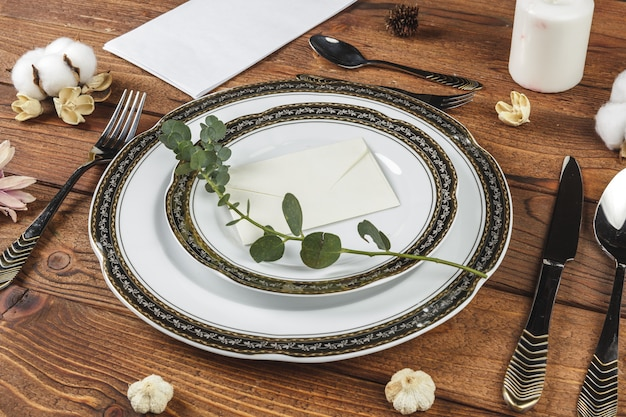 Vintage table setting on wooden table with floral decor