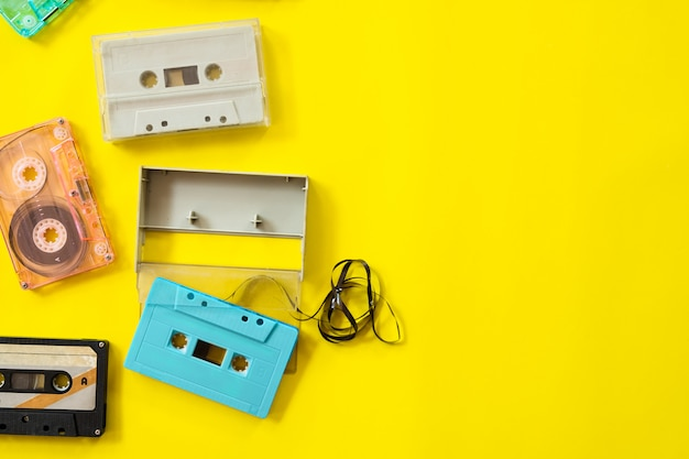 Vintage tape cassette recorder on yellow background, top view. retro technology.