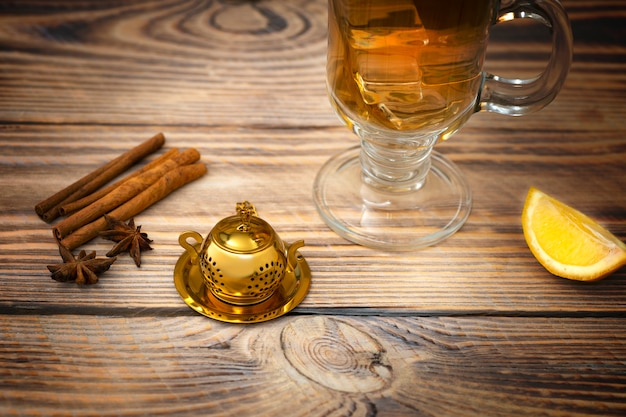 Vintage tea strainer and glass of tea on a wooden table with lemon and cinnamon