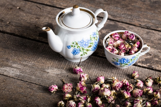 Vintage teapot and cup with blooming tea flowers on wood