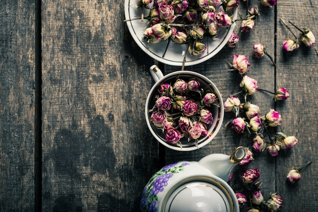 Vintage teapot and cup with blooming tea flowers on wooden background