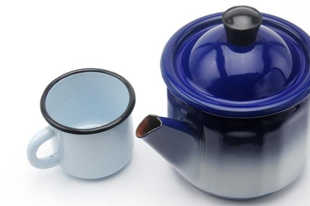 Винтажный чайник в синем с кружкой на изолированном белом
