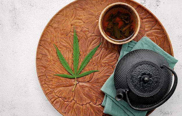 Vintage teapot with cannabis herbal tea  set up on concrete background.