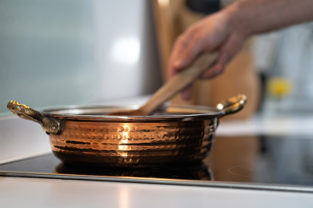 Vintage textured copper cooking pot on kitchen with male hand cooking