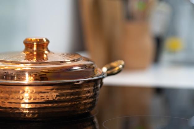 Винтаж текстурированный медный котелок на кухонной плите