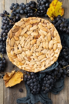 Vintage textured rattan plate and grape wine on old wooden