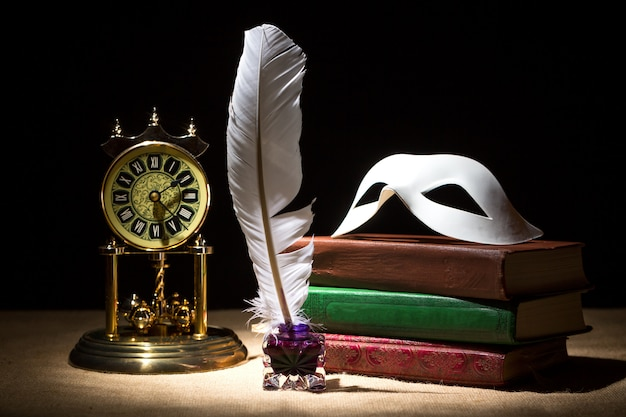 Vintage theater mask on old books near inkstand with feather and old clock against black background