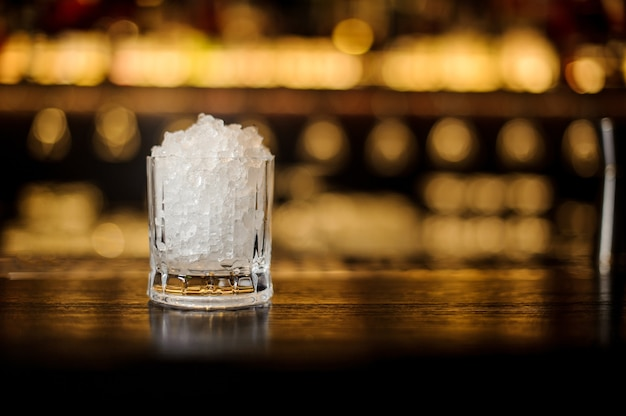 Винтажный толстостенный коктейльный бокал с колотым льдом, стоящий на пустой стальной барной стойке
