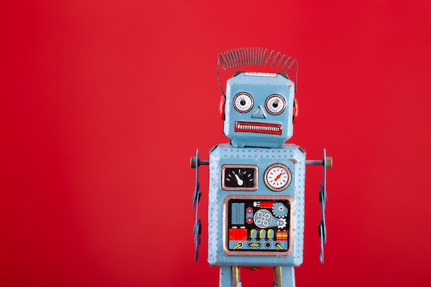 Vintage tin toy robot on red background