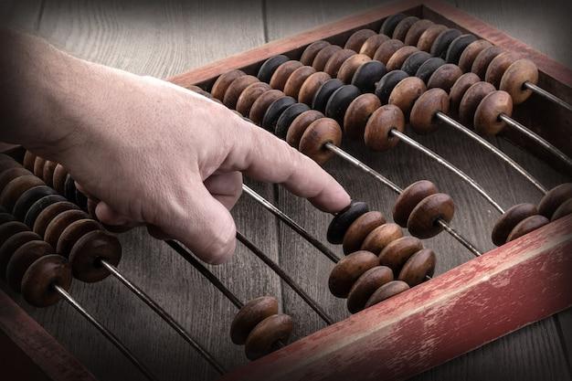 오래된 주판 .financial 개념 디자인을 사용한 남자 손 회계의 빈티지 톤.