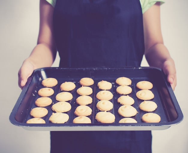 Vintage tone of woman holds freshly baked cookies on a baking tray