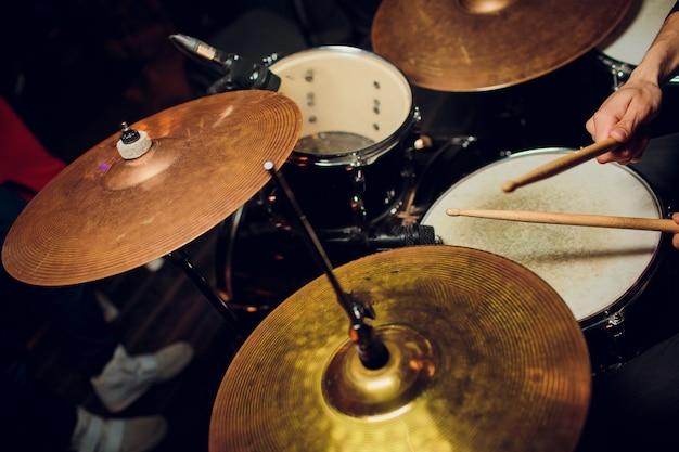 ビンテージトーンのライブ音楽の背景、ドラマーはロックドラムセットでばち状核突起で遊ぶ
