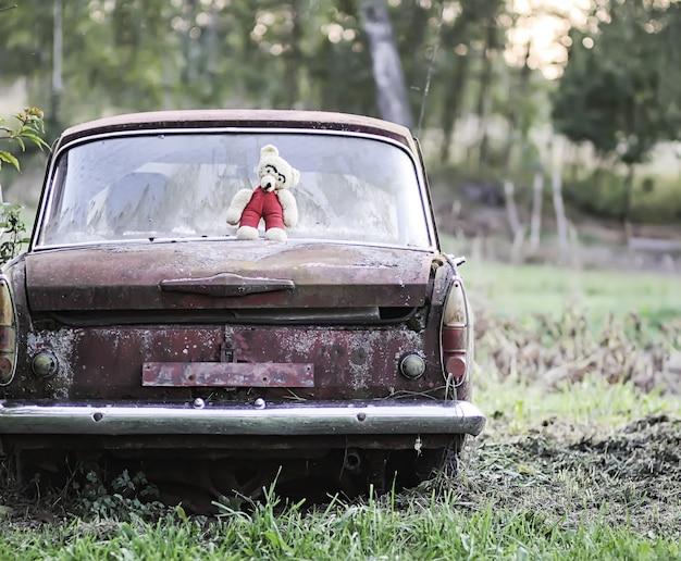 복고풍의 녹슨 자동차 야외에 있는 오래된 곰 장난감의 빈티지 사진