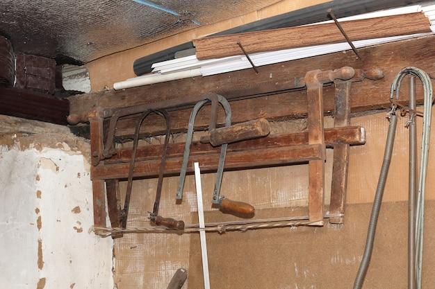 Старинные инструменты, висящие на стене в сарае для инструментов или мастерской