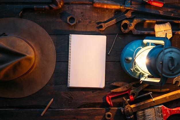 ビンテージツールセットと大工の仕事机の上のコピースペースを持つ空のノートブックページ
