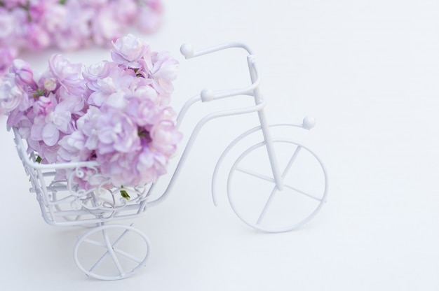 Vintage toy bike white. bouquet of lilac, holiday decoration.