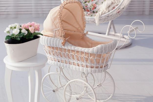 Винтажная игрушечная коляска в белом интерьере. детство