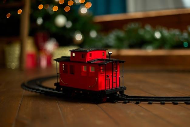 ヴィンテージの電車の車は、ライトの花輪の背景にクリスマスツリーの下の床にあります