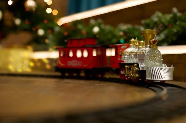 ヴィンテージ列車は、ライトの花輪を背景にクリスマスツリーの下の床にあります