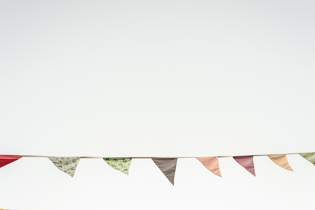 Vintage triangular pennants hanging with the blue sky in the background.