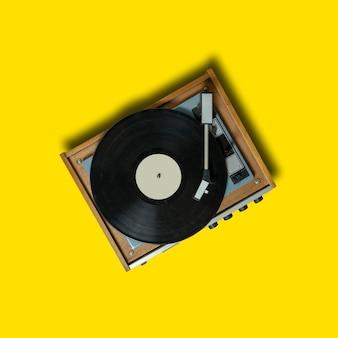 黄色の背景にビンテージターンテーブルビニールレコードプレーヤー。音楽を再生するレトロなサウンドテクノロジー