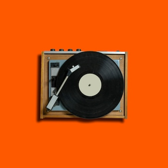 Vintage turntable vinyl record player on orange