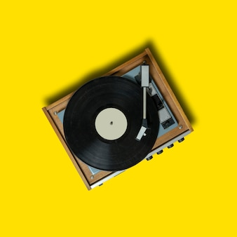 Vintage turntable vinyl record player on yellow background. retro sound technology to play music