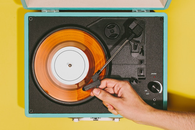 Vintage turntable with a hand and orange vinyl disc