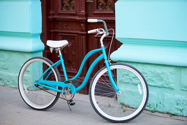 Vintage turquoise bicycle with white elements parked near old building with turquiose walls and brown wooden antique doors.