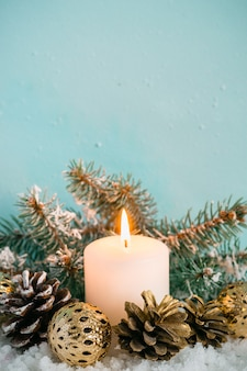 Vintage turquoise christmas greeting card. candle and conifer on snow background