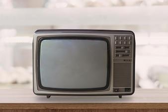 ぼかしの背景と木製のテーブルにヴィンテージテレビボックス。