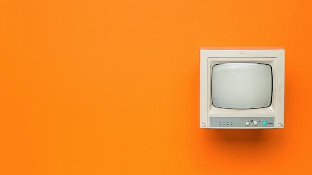 오렌지 배경에 빈티지 tv입니다. 텍스트를 위한 공간입니다. 플랫 레이.