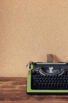 コルク板の壁の背景の表面の近くの木製のテーブルでヴィンテージタイプライター