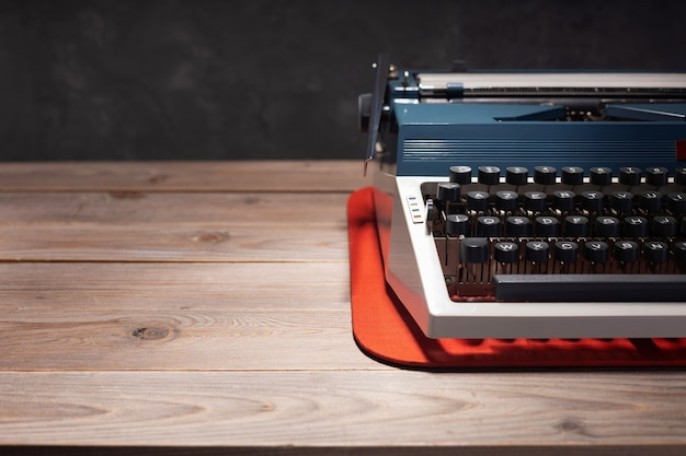 Винтажная пишущая машинка на деревянном верхнем столе возле поверхности фона стены, сценарист или ретро-писатель