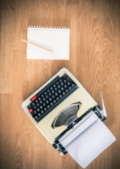 Vintage typewriter and a blank notebook of paper