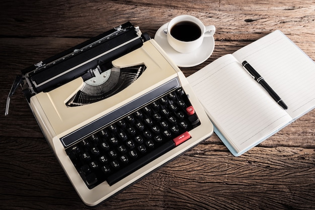 Vintage typewriter and a blank notebook , pen and coffee cup, retro colors