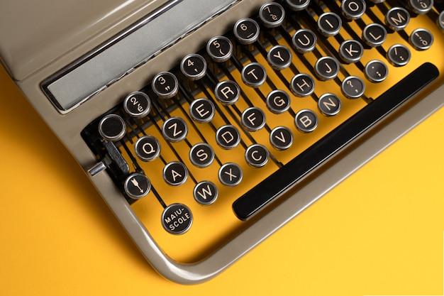 Старинная пишущая машинка на желтом фоне