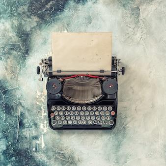 Винтажная пишущая машинка с шероховатым бумажным листом. тонированная картина в стиле ретро