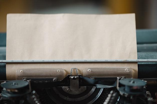 Винтаж пишущая машинка с вставленным листом коричневой бумаги