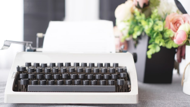Vintage typewriter with paper. retro machine technology - white background with flowers