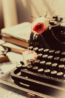 Vintage typewriter with pink rose, old books on table.