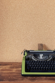 Vintage typewriter at wooden table near cork board wall background surface