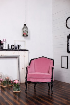 Vintage velor armchair, in a bright room and an artificial fireplace. interior attic with wooden white walls. picture frames on the wall. the space where you can put a person. gothic style room.
