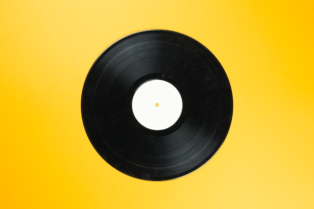 Vintage vinyl record disk with empty white label on orange background. retro sound technology to play music