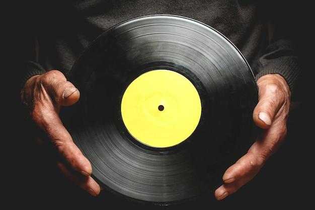 老人の手にビンテージビニールレコード