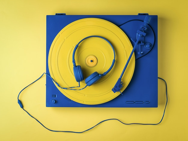 Vintage vinyl record player and blue headphones on a yellow background. retro music equipment.